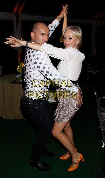 "Louie Spence & Lisa Maxwell .At the After Party for ""Shrek The Musical"" Press Night, Somerset House, London, England, UK, June 14th 2011..full length black white polka dot shirt hand on hip print top grey gray ruffle skirt tiered  bow belt sash orange shoes  dancing holding hands funny side arm .CAP/COA/CC.©CC/COA/Capital ."