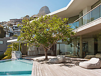 The contemporary home has a relaxed, peaceful quality with a seamless connection between indoor and outdoor living. A tree provides a shady spot on the cantilevered terrace beside the pool.