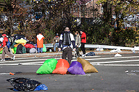 Volunteers and independent contractors help gather discarded clothing and other trash littering the on-ramp to the Verrazano-Narrows Bridge after the start of the ING New York City Marathon on Staten Island on 07 November 2010.