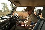 Cheetah (Acinonyx jubatus) biologist, Jake Overton, entering data during transect, Kafue National Park, Zambia