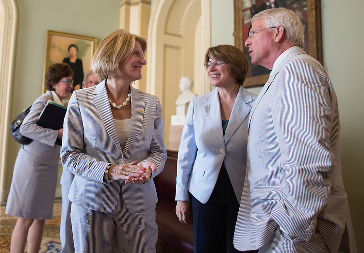 UNITED STATES - JUNE 11 - Sen. Shelley Moore Capito, R-W.V., left, speaks with Amy Klobuchar, D-Minn., and Sen. Roger Wicker, R-Miss, after they take a group photograph in the Ohio Clock Corridor in celebration of National Seersucker Day on Thursday, June 11, 2015. Continuing the tradition introduced by Sen. Trent Lott (R-MS) in 1996, Dr. Cassidy reintroduced National Seersucker Day in the U.S. House of Representatives in 2014 and is continuing the tradition in the U.S. Senate. (Photo By Al Drago/CQ Roll Call)