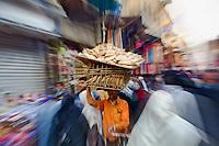 Blurred motion effect, young man carrying bread through Khan el Khalili Bazaar, Cairo, Egypt