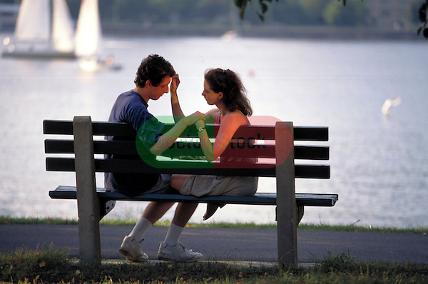 young woman comforting young man on park bench