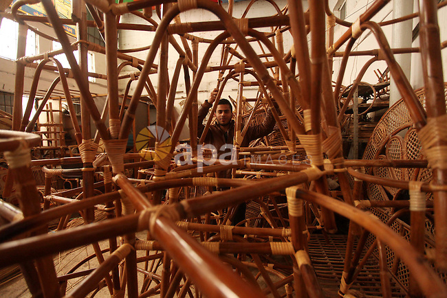 A Palestinian man sorts bamboo charis at a workshop in Gaza city on April 16, 2015. Bamboo is a product of southeast Asian countries and before the Israeli blockade of the Gaza Strip, Gaza traders used to bring it in to the coastal territory in adequate quantities to allow the industry to remain viable. The traditional industry fade away gradually due to economic instability in the region and the lack of training for the industry across the Gaza Strip. Photo by Ashraf Amra