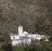 Ferreirola village with church tower, Taha Valley, Alpujarra, Andalucia, Southern Spain. Moorish influence is seen in the distinctive cubic architecture of the Sierra Nevada's Alpujarra region, reminiscent of Berber architecture in Morocco's Atlas Mountains. Photograph by Manuel Cohen.
