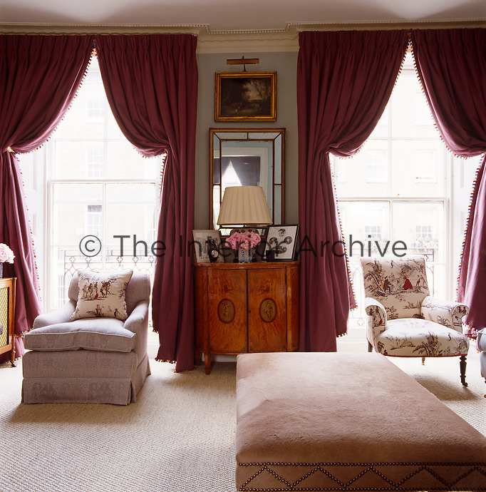 The elegant drawing room is graced with linen curtains and is light and feminine