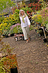 A woman pulling a wagon full of flowers though a gravel-floored garden shop.