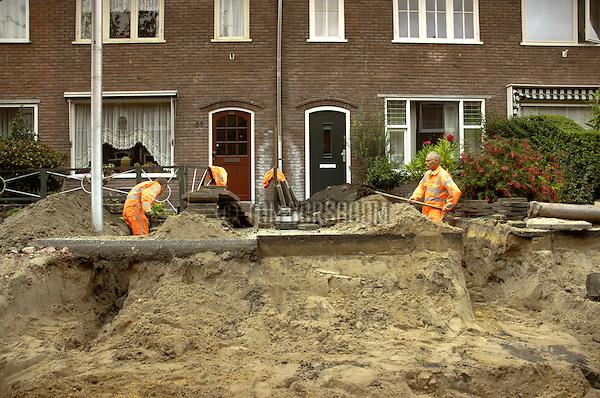 UTRECHT - In de Utrechtse Schepenbuurt zijn medewerkers van Bam Wegen bezig met het moeilijkste deel van de aanleg van een nieuw vuilwater- en hemelwaterriool: het graven van een geul in de voortuin van de rioolbuis naar de regenpijp. Om het relatief schone hemelwater niet onnodig via het vuilwaterriool weg te laten lopen, is de gemeente Utrecht begonnen water uit de regenpijp via speciale straatkolken (waterputten) door een zandfilter, naar het Amsterdam-Rijnkanaal af te voeren. Dit is niet alleen goed voor het grond- en oppervlaktewater maar voorkomt daarnaast bij hevige regenval ook wateroverlast en overloop van het vuilwaterriool. Hoewel het meeste werk zoals het uitgraven van de straat en aanleg van de grote rioolbuizen met hulp van machines wordt gedaan, blijft het precaire werk - het tussen de leidingen en wortels van de tuinplanten heen graven - voorbehouden aan zorgvuldig mensenwerk: scheppen met de schop. COPYRIGHT TON BORSBOOM