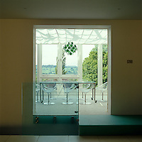 A view through to the conservatory dining room furnished with Philippe Starck Eros chairs and a 1950's style chandelier