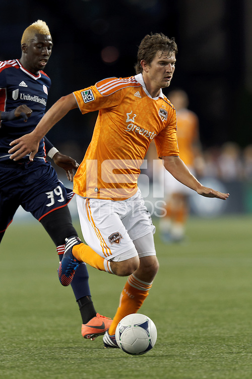 Houston Dynamo defender Bobby Boswell (32) brings the ball forward as New England Revolution forward Saer Sene (39) closes. In a Major League Soccer (MLS) match, the New England Revolution tied Houston Dynamo, 2-2, at Gillette Stadium on May 19, 2012.