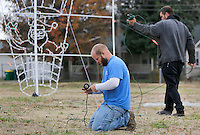 NWA Democrat-Gazette/DAVID GOTTSCHALK  Dustin Davis (left) and Daniel Sims, both maintenance two workers with the city of Springdale Parks and Recreation Department, string an extension cord Wednesday, November 25, 2015, from the Hot Air Balloon light display in downtown Springdale. The holiday decoration is one that is being relocated from Murphy Park to areas of downtown Springdale because of work taking place in the park.