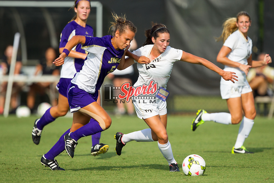 Kendall Fischlein (23) of the Wake Forest Demon Deacons is fouled by Sam Lofton (5) of the James Madison Dukes during first half action at Spry Soccer Stadium on August 29, 2014 in Winston-Salem, North Carolina.  The Dukes defeated the Demon Deacons 2-1.   (Brian Westerholt/Sports On Film)
