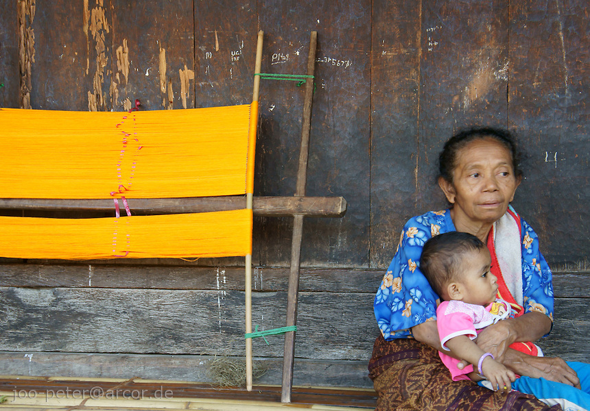 woman and child on veranda of her house next to  weaving tools in  famous traditional village Wolotopo, close to harbor city Ende on island  Flores in archipelago of Indonesia
