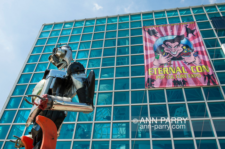 Garden City, New York, USA. June 14, 2015. TThe tall Robotman metal sculpture, by artist C. Evan Gray, is on display outdoors in front of the Eternal Con banner on the glass facade of the Cradle of Aviation Museum, at Eternal Con, the Long Island Comic Con. The sculptor created it from automotive and other parts.