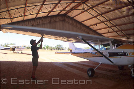 "Pilot Mark O'Kane with plane in hangar at ""Bulloo Downs"" station, near Thargomindah, far west Queensland."