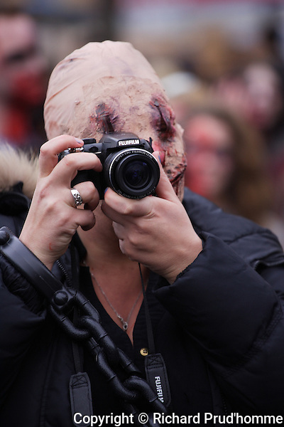 A  male zombie taking photos with a camera
