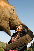 """Owner Lek with rehabilitated 3 year old """"Hope"""" at Elephant Nature Park, Thailand."""