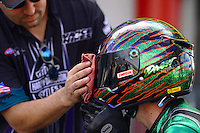 Sept. 14, 2012; Concord, NC, USA: A crew member cleans the helmet visor of NHRA pro stock motorcycle rider Andrew Hines during qualifying for the O'Reilly Auto Parts Nationals at zMax Dragway. Mandatory Credit: Mark J. Rebilas-
