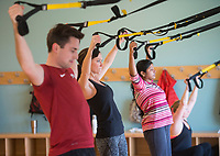 NWA Democrat-Gazette/BEN GOFF @NWABENGOFF<br /> Patrick Joseph (from left), of Bentonville, Ally Renner of Fayetteville and Saritha Thummeti of Bentonville take part in a TRX fitness class Wednesday, Jan. 3, 2018, at the Bentonville Community Center.