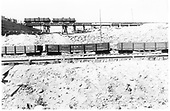 Side view of three D&amp;RG gondolas, #8215, #8899 and #8320, at Salida.  Two other gondolas, #8483 and an unidentified one, are on a trestle in the background with men either unloading their contents or cleaning the cars.<br /> D&amp;RG  Salida, CO  Taken by Meigs, N. W. - ca. 1890