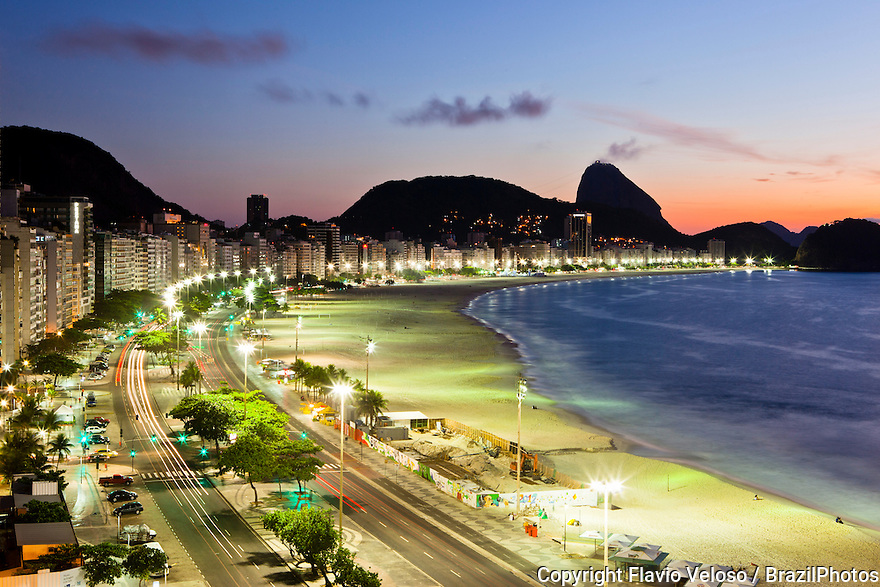 Sunrise at Copacabana beach, Atlantica avenue, Sugar Loaf mountain in background - the promenade is a pavement landscape in large scale ( 4 kilometres long ) having a black and white Portuguese pavement design  by Roberto Burle Marx, a geometric wave.  Rio de Janeiro, Brazil.
