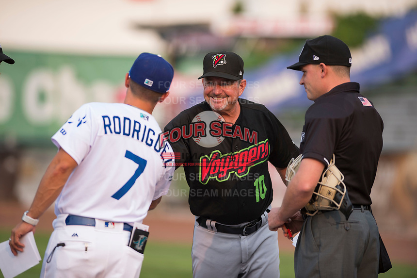 Great Falls Voyagers manager Tim Esmay (10) shakes hands with Jeremy Rodriguez (7) as home plate umpire Bobby Tassone looks on before a Pioneer League against the Ogden Raptors at Lindquist Field on August 23, 2018 in Ogden, Utah. The Ogden Raptors defeated the Great Falls Voyagers by a score of 8-7. (Zachary Lucy/Four Seam Images)