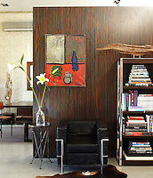A wooden partition separating the hall from the dining room displays a painting by Gustavo Serra and an LC2 chair by Cassina