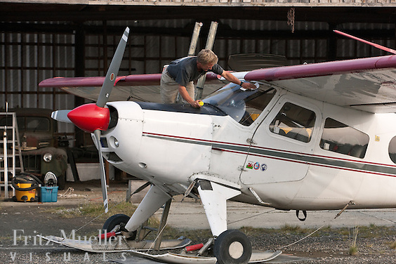 Lance Goodwin maintaining Helio Courier airplane at Kluane Lake Research Station