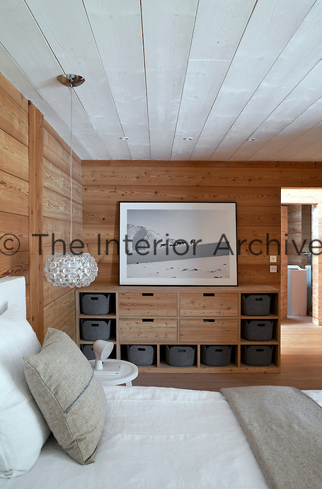The wood-clad wall of the bedroom is lined with an integrated storage unit above which hangs a black and white photograph by Patrick Blin