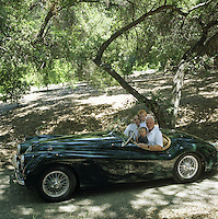 Malcolm McDowell and his family in a vintage Jaguar in the California oak woods that surround his home