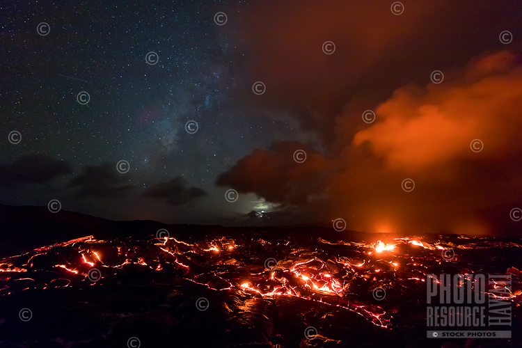 As the moon sets, a shooting star heads towards orange-lit clouds over molten lava rivers in Pulama Pali (of Holei Pali), Hawai'i Volcanoes National Park, Puna, Hawai'i Island, September 2017.