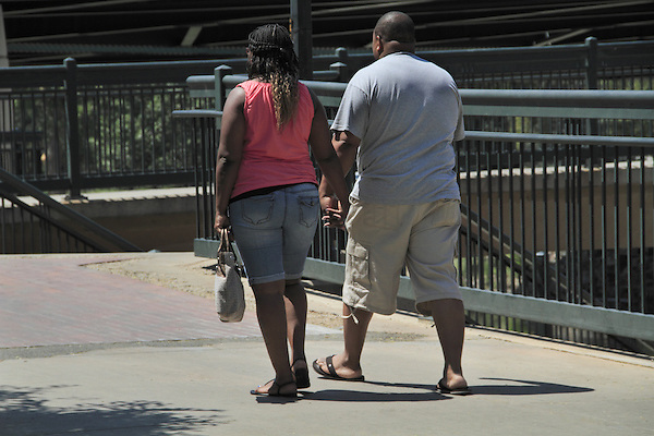 Black woman and man hold hands while walking in Denver, Colorado. .  John offers private photo tours in Denver, Boulder and throughout Colorado. Year-round Colorado photo tours.