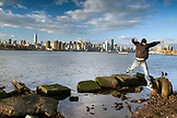 USA, New York, Man jumping the edge of the East River in Brooklyn with the New York City skyline in the distance, East River State Park