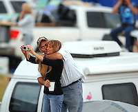 A couple of race fans snap a souvenir photograph of themselves before the start of the Budweiser Shootout at Daytona International Speedway in Daytona Beach, Fl. (The Florida Times-Union, Rick Wilson)