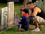 Photo by Phil Grout..Cub scout Rene Herbst IV gets a history/patriotism lesson from.his father, Rene III, after the scout plants a flag at the tombstone.of Daniel Bowman at the Trinity Lutheran Church cemetery in.Manchester.  Bowman, who was born in 1783, possibly fought in.the War of 1812.  Herbst is a U.S. Army veteran.  The two were.participating in a Memorial Day observance lead by cub pack.320.
