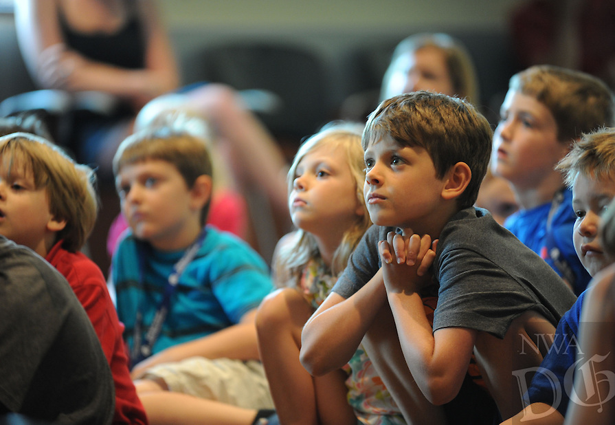 STAFF PHOTO ANDY SHUPE - Aidan Thomas, 9, of Fayetteville listens to music performed by Joe Crookston of Ithaca, Ny., Wednesday, July 9, 2014, during a concert for kids at the Fayetteville Public Library. Crookston will perform at 10:30 a.m. today at a family concert and conduct songwriting workshops during the day before hosting a culminating concert at 6:30 p.m. A concert is also planned for 7 p.m. Friday.