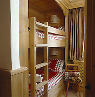 The children's bedroom has space-saving pine bunks set into a niche in the pine panelling