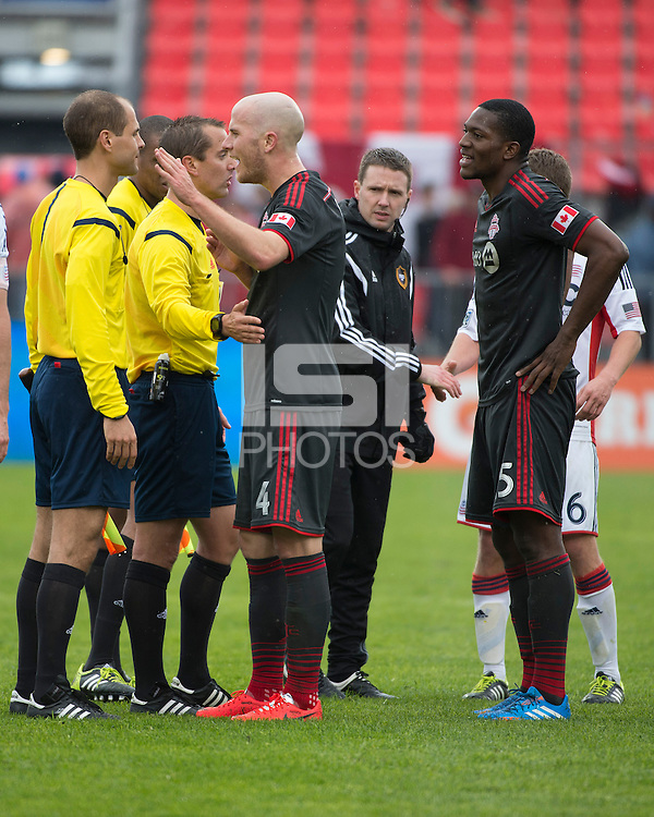 Toronto, Ontario - May 3, 2014: Toronto FC midfielder Michael Bradley #4 and Toronto FC defender Doneil Henry #15 talk with the officials after the final whistle during a game between the New England Revolution and Toronto FC at BMO Field.<br />