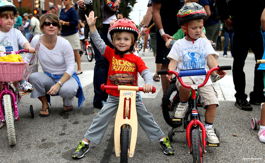 Brisbane LaBarre-Gurski, 3, of Portsmouth, left, waves before the start of the Portsmouth Criterium 4-6 year-olds race in Portsmouth, N.H., Sunday, Sept. 9, 2012. (Portsmouth Herald Photo Cheryl Senter)
