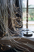 The fibre-optic chandelier which hangs over the steel dining table was designed by David Emery