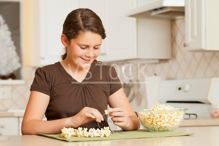 USA, California, Lawndale, Girl (10-11) sewing popcorn onto string