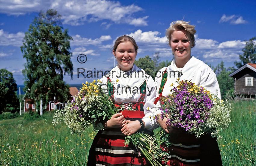 Sweden, Province Darlana, young women gathering flowers for midsummer celebration | Schweden, Provinz Darlana, einhimische, junge Frauen in Landestracht sammeln Wiesenblumen fuer das Mittsommerfest