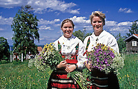 Sweden, Province Darlana, young women gathering flowers for midsummer celebration | Schweden, Provinz Darlana, einhimische, junge Frauen in Landestracht sammeln Wiesenblumen fuer das Mittsommerfest