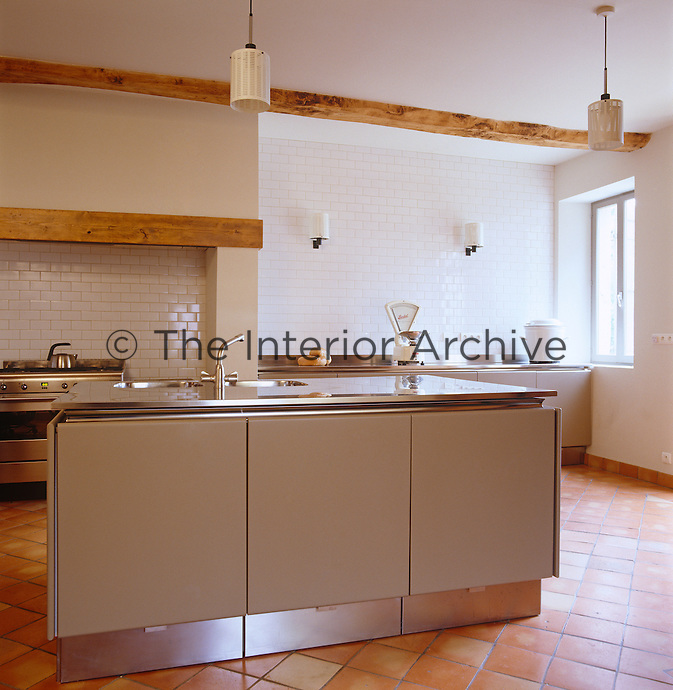 This brushed steel kitchen with ceramic tiled walls and terracotta floor is by Tinsettanta