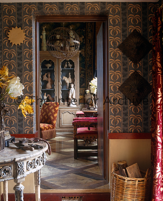 The wooden floor of the living room glimpsed through the open door from the hall has been painted in trompe l'oeil marble tiles