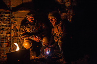 Two soldiers of the Mohammed Said checkpoint in Kunar are trying to warm them up with a fire during their shift at the third tower, Kunar, Afghanistan, 15th November 2017. <br /> <br /> Deux soldats du poste avancé Mohammed Said à Kunar tentent de se réchauffer avec un feu pendant leur shift à la troisième tour, Kunar, Afghanistan, 15 novembre 2017.