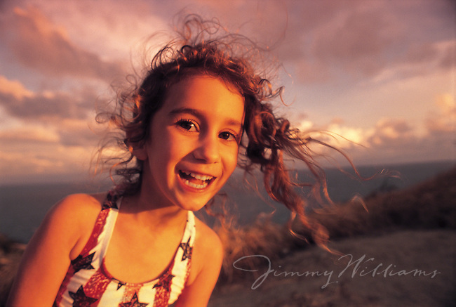 A young girl smiles as her hair blows in the wind on a beach at sunset.