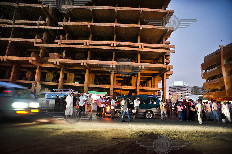 People and buses in front of a part-built, high rise building whose construction has been put on hold. Sudan has lost billions of dollars in oil receipts since the south gained independence in 2011 resulting in soaring prices and a weakening currency.