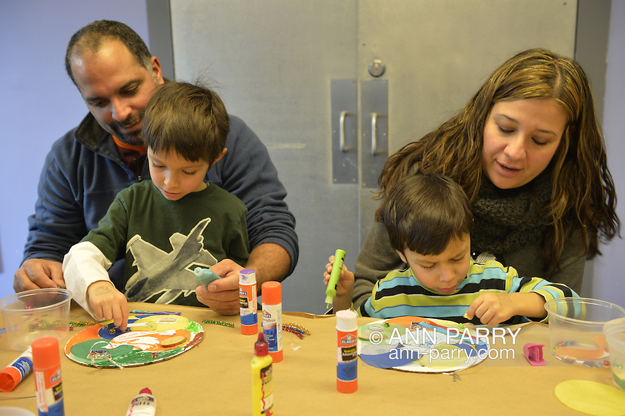 Garden City, New York, U.S. January 20, 2014. L-R, JESSE RIVERA; son JADEN RIVERA, 4; wife ALEXANDRA RIVERA; and son JACOB RIVERA, 5, of Sea Cliff, create artwork of peace at the program Dreaming with Dr. Martin Luther King, Jr. where children also explored Dr. King's life, at the Long Island Children's Museum, to celebrate the American official federal holiday Birthday of Martin Luther King, Jr.