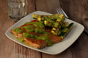 Grilled salmon fillet served with pesto sauce and zucchini sticks